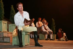 Nick Sandys, a tall man with wavy red-brown hair and wearing a white blouse, yellow trousers, and black boots, sits on a green crate with a brown book in hand, while a cast of men dressed in 18th century costumes converse behind him