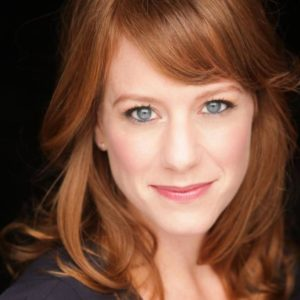Melanie Keller, a young woman with light skin, copper-red hair, and blue-gray eyes.