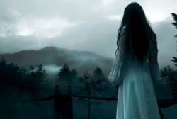 A long dark-haired woman in a long white dress looks out over a foggy, desolate landscape tinted blue.