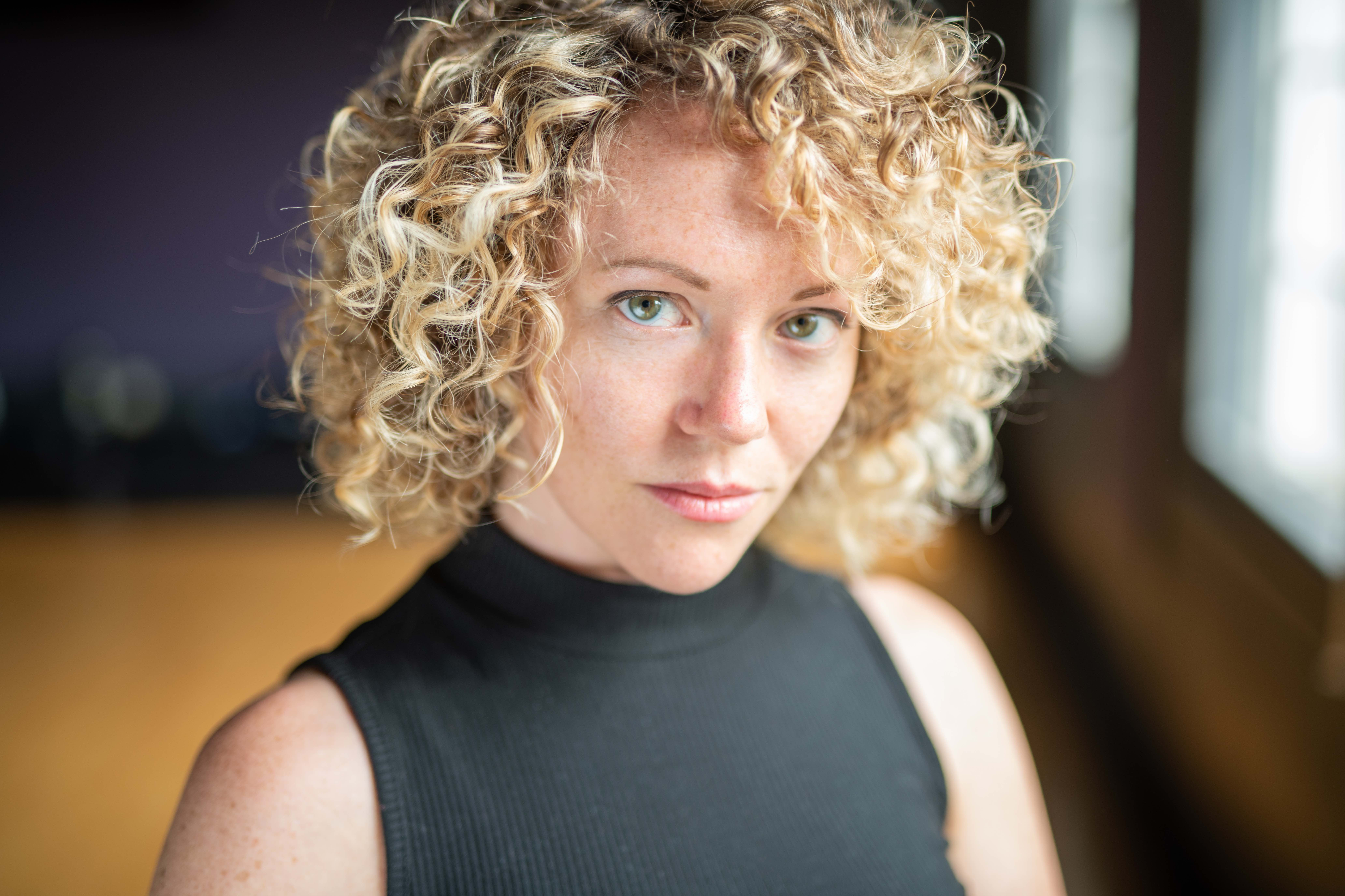 Courtney Abbott, a woman with curly blonde hair and blue eyes.